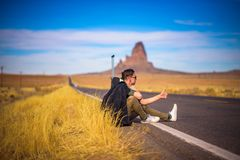 Free Tired Hitch-hiker With Suitcase Sitting On A Road Stock Image - 114962011