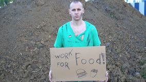 Tired hobo man on the street. Sign on cardboard - will work for food stock video