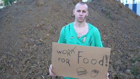 Tired hobo man on the street. Sign on cardboard - will work for food stock footage