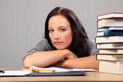 Tired from homework woman rests chin on desk Stock Image