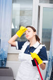 Tired hot housekeeper wiping her forehead Stock Photo