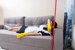Tired housekeeper relaxing on the job. Tired housekeeper or maid in uniform relaxing on the job lying on a couch covering her eyes for a nap with her mop Stock Photos