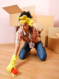 Tired housewife. Tired young woman with yellow rubber gloves scrubs the floor Stock Images