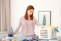 Tired housewife with basket full. Of clothes prepared for ironing at home Royalty Free Stock Photo