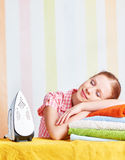 Tired housewife fell asleep on ironing board with iron Stock Image