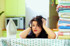 Tired housewife after ironing clothes, home interior Stock Images