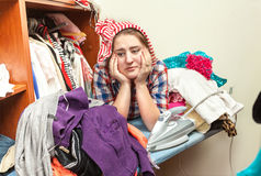 Tired housewife in pile of not ironed clothes Stock Image