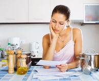 Tired housewife reading bills Royalty Free Stock Images