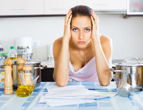 Tired housewife reading bills Royalty Free Stock Image