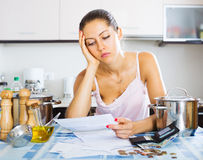 Tired housewife reading bills Royalty Free Stock Photos