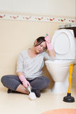 Tired housewife at the toilet. Tired housewife ath the toilet with brush Royalty Free Stock Images