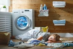 Tired housewife woman in stress sleeps in laundry room with wash Royalty Free Stock Image