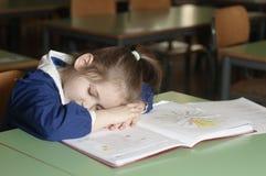 Tired italian elementary school girl first-grader on school de Royalty Free Stock Image