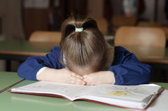 Tired italian elementary school girl first-grader on school de Stock Image