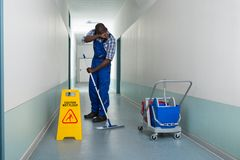 Tired Janitor Cleaning Floor. Tired Male Janitor With Cleaning Equipment And Wet Floor Sign In Corridor Stock Photos