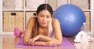 Tired Japanese woman lying on workout matt Stock Photo