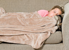 Tired Kid. A young girl is covered with a blanket on the sofa and about to take a nap Royalty Free Stock Photography