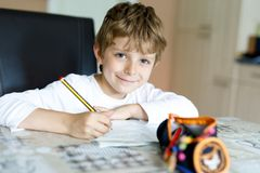 Tired kid boy at home making homework writing letters with colorful pens Royalty Free Stock Photography