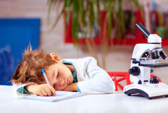 Tired kid fell asleep after conducting experiment in school lab Royalty Free Stock Photos