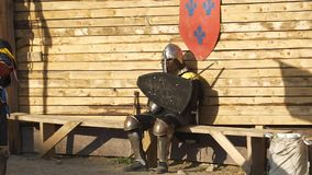Tired knight resting in the bench after the battle
