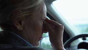 Tired lady driver stacking in traffic jam taking off eyeglasses, massaging nose