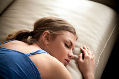 Tired lady falling asleep after sleepless night. Tired young woman sleeping on couch, resting at home after busy day at work. Stressed lady falling asleep after stock image