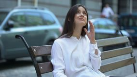 Tired lady sitting on bench, suffering from head ache, meteorological dependence