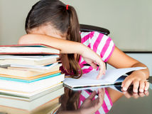 Tired latin schoolgirl sleeping on her desk Royalty Free Stock Images