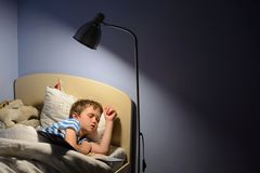 Tired little boy child fell asleep. During reading a book in bed Stock Photos