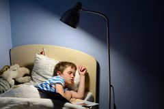 Tired little boy child fell asleep. During reading a book in bed Royalty Free Stock Image