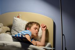 Tired little boy child fell asleep. During reading a book in bed Royalty Free Stock Photo