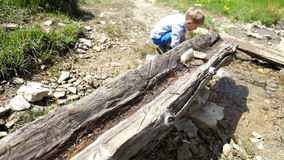 Tired little boy drinks from mountain creek stock footage