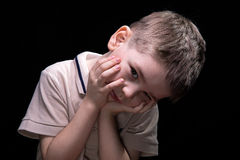 Tired little boy with hands on face. On black background Stock Images
