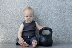 Tired little boy after pumping iron with a kettlebell sitting on the floor. An infant boy sits with a big weight and looking at camera Stock Photography