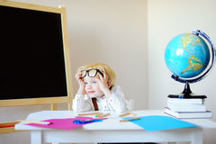 Tired little boy at school workplace Royalty Free Stock Photography