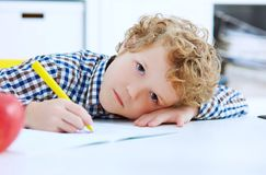 Tired little boy sitting at the table, with hishead on his arm,. Writing in her notebook while doing homework. Concept of a large number of assignments at Royalty Free Stock Photos