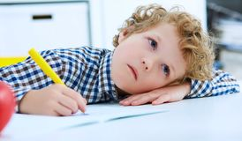 Tired little boy sitting at the table, with hishead on his arm,. Writing in her notebook while doing homework. Concept of a large number of assignments at Royalty Free Stock Images