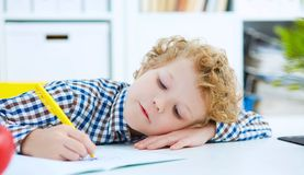 Tired little boy sitting at the table, with hishead on his arm,. Writing in her notebook while doing homework. Concept of a large number of assignments at Stock Images