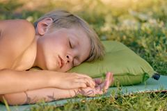 Boy sleeping outdoor on tourist pillow. Tired little boy sleeping after playing outdooron tourist pillow Stock Photography