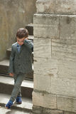 Tired little boy stands near the old wall with staircase. Tired little boy stands near the old stone wall with stairs Stock Photos