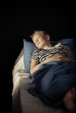 Tired little boy in striped shirt sound asleep. In bed with blue pillow and sheet Stock Photo