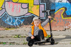 Tired little boy with a sulky. Expression sitting holding onto his scooter in front of a brightly coloured wall covered in graffiti Stock Photos