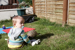A tired little boy with a tortoise. A tired little boy sitting on the grass  with a tortoise Stock Photography