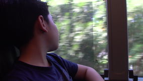 Tired little boy travelling in bus and looking through the window stock footage