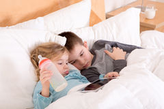 Tired little brother and sister going to sleep. Lying close together in a warm comfortable bed with a tablet computer on which they have just read a bedtime Stock Images