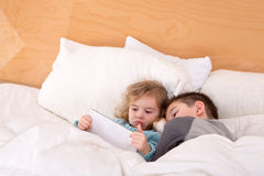 Tired little brother and sister in a warm bed. Tired little brother and sister snuggling up together in a warm comfortable bed as they read a bedtime story on a Stock Image