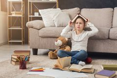 Little female child reading book while sitting on the carpet stock photo
