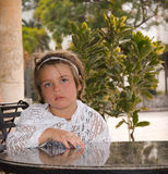 Tired little child sitting in garden behind the table Royalty Free Stock Photography