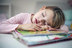 Tired little dreaming on book girl. royalty free stock photography