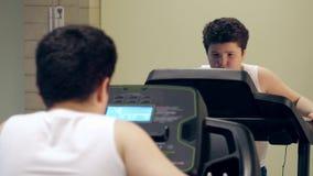 Tired little fat cute boy walking on treadmill in the gym indoors. Tired little fat boy walking on treadmill in the gym indoors stock video footage